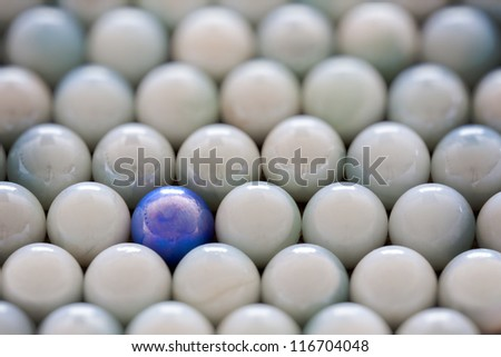 pale opal marbles displayed with one blue marble standing out as abstract - stock photo