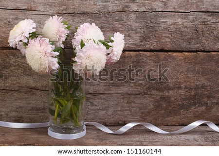 Pale pink asters in a glass vase with a ribbon on a background of the old wooden wall