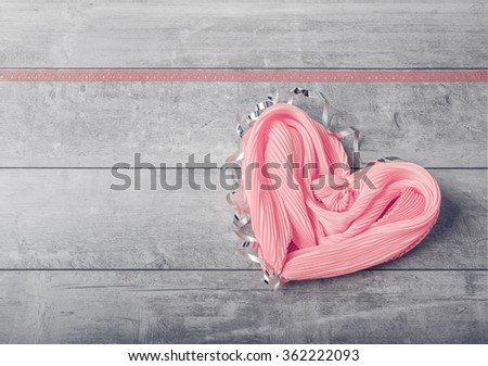 Pale pink silk scarf laid in the shape of a heart on a gray wooden background
