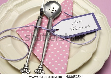 Pale pink theme wedding table place setting with polka dot napkin and antique silverware with Just Married tag. Close up. - stock photo