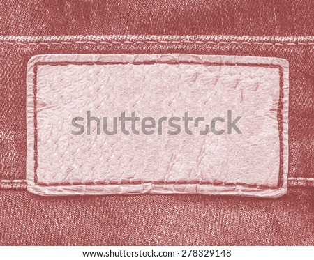 pale red leather label on red jeans background - stock photo