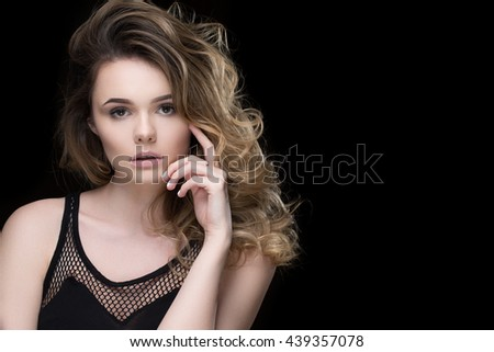 Pale skinned queen. Portrait of a stunning young fashion model with massive curly hairstyle looking to the camera seductively touching her face copyspace on the side  - stock photo