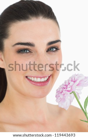 Pale woman showing a flower while smiling