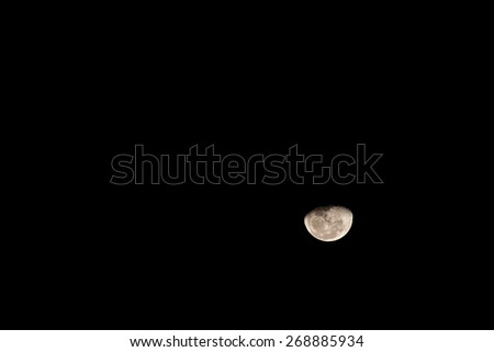 pale yellow moon on a full moon against a black sky - stock photo