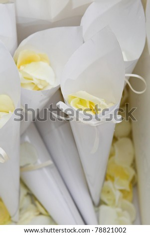 Pale yellow rose petals in confetti cones with satin ribbon bows - stock photo