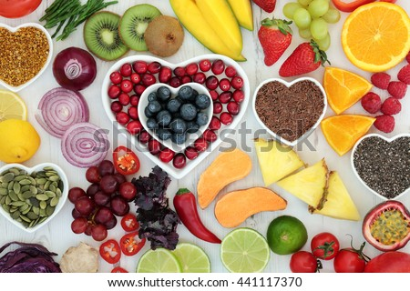 Paleo diet health and superfood of fruit, vegetables, nuts and seeds in heart shaped bowls on distressed white wood background, high in vitamins, antioxidants, dietary fiber and minerals. - stock photo