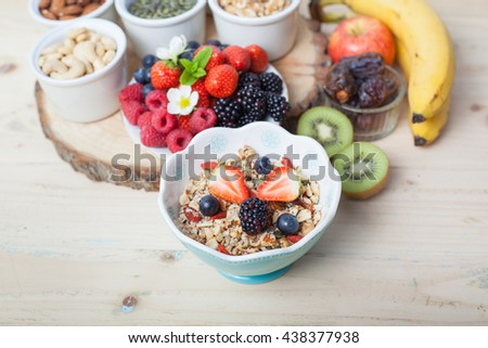 Paleo style breakfast: gluten free granola with mixed nuts, and fresh berries and fruits, selective focus on a blackberry