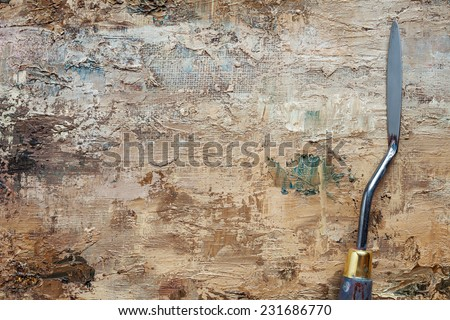 palette knife on linen artist canvas with coating of brown oil paint - stock photo