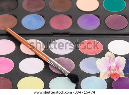 Palette of colorful eye shadow with a brush for makeup and orchid flower. Makeup background. - stock photo