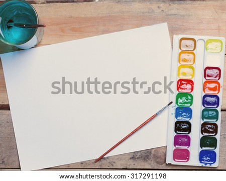 palette of watercolor paints, glass of water and a piece of blank paper on the table.toned.top view - stock photo