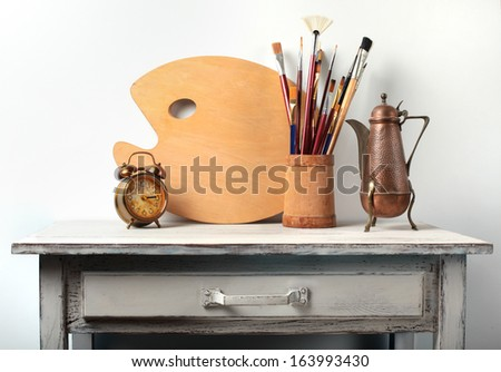 palette with brushes and an alarm clock on the table - stock photo