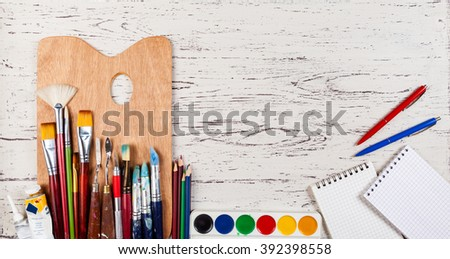 palette with brushes and paints on a wooden table - stock photo