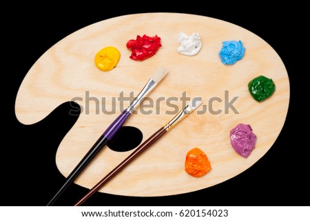 Palette with multicolored paints and artistic brushes on a black background