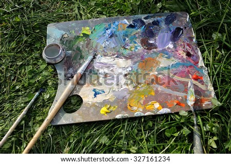 Palette with oil paints in the grass, background, texture, backg