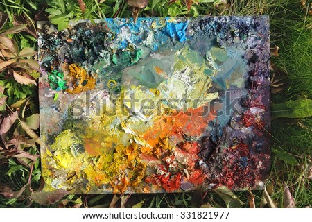 Palette with oil paints in the grass, background, texture, background