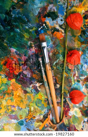 palette with paintbrushes and physalis - stock photo