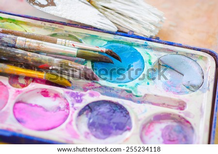 palette with watercolor ink and brush - stock photo