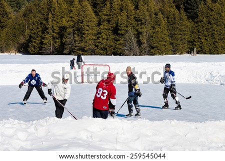 PALGRAVE, ONTARIO - MARCH 8: Outdoor enthusiasts playing a friendly game of ice hockey on an outdoor skating rink in Palgrave village in Ontario on March 8, 2015.