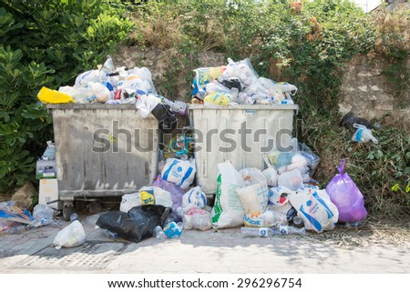 PALIOURI , GREECE - JULY 13 2015 : Rubbish bins overflow with rubbish and thrown on the floor. The bins have not been emptied for days - stock photo
