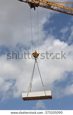 pallet of plasterboards at crane hook - stock photo