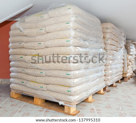 Pallets of wood pellets in plastic bags - stock photo