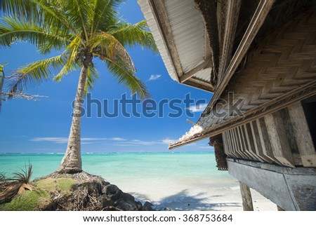 palm bungalow on  white sand beach with palm tree and view on azure sea  in polynesia - stock photo