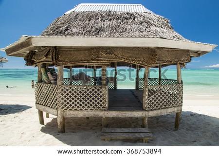palm bungalow on  white sand beach with view on azure sea  in polynesia - stock photo