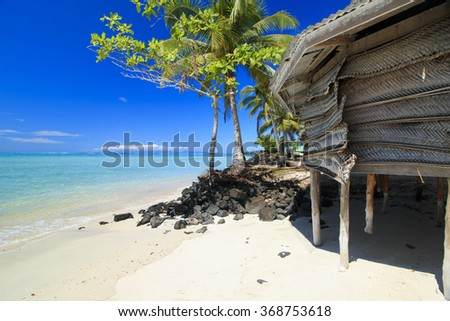 palm bungalows on  white sand beach with palm tree lava stones and view on azure sea  in polynesia - stock photo
