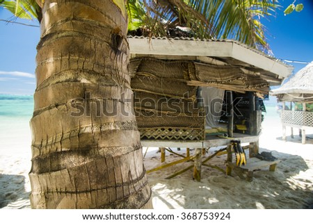 palm bungalows on  white sand beach with palm trees and view on azure sea  in polynesia - stock photo