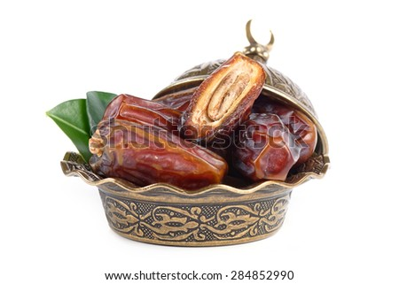 Palm dates on the bronze plate, white background - stock photo