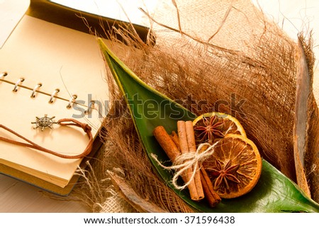 Palm leaf on the bark of a palm with two slices of dried orange and cinnamon sticks with a notebook bound in leather