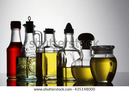 palm oil, sesame seed oil, olive oil, grape seed oil and corn oil in  glass bottle over white background - stock photo