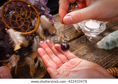 Palm reading, characterization and foretelling the future through the study of the palm with pendulum - stock photo