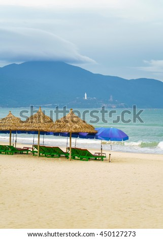 Palm shelter and umbrellas with sunbeds in the China Beach in Danang, Vietnam. It is also called Non Nuoc Beach. South China Sea and Marble Mountains on the background.