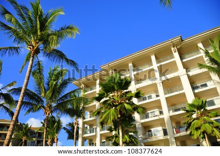 Palm trees on Maui along the Kaanapali beach front walking path with luxury hotel and condos in view. - stock photo