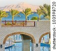 Palm trees, Red Sea, mount, bridges and swimming pool - stock photo