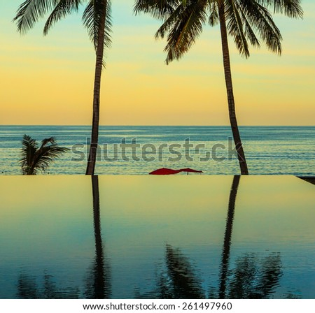 Palm trees reflected in smooth water of the pool on the beach. Delicate sunset on the popular resort island of Koh Samui - stock photo