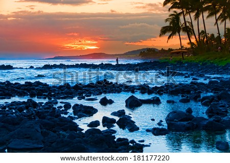 Palm trees silhouetted against a colorful tropical sunset and reflected in the Pacific Ocean on the island of Kauai, Hawaii, USA - stock photo