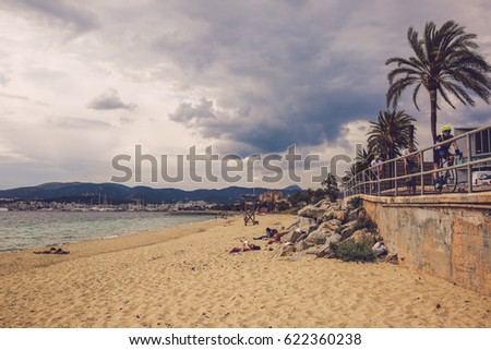 PALMA DE MALLORCA, SPAIN - April 5, 2017: Cloudy day in Palma with tourists on the sand beach, cyclists riding past and the cathedral in the background