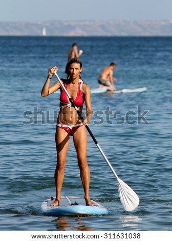 PALMA NOVA BEACH, MAJORCA, SPAIN - 25th August 2015: Palma Nova beach resort on the 25th August 2015. A young woman is paddle boarding in the foreground. - stock photo