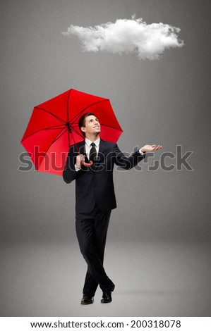 Palming up man with opened umbrella checks the rain and looks at the cloud overhead, isolated on grey - stock photo
