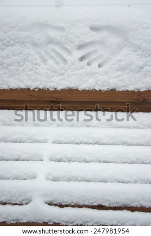 palms imprint on a newly-fallen snow, on a wooden bench at a park lane - stock photo