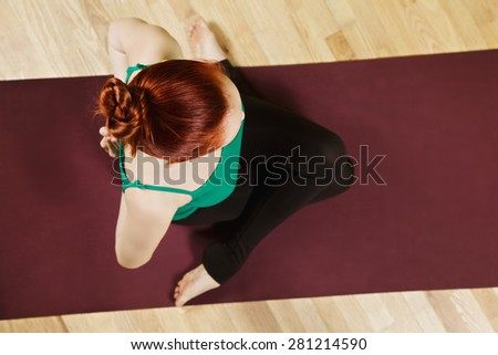 Palms of redhead caucasian woman folded behind back exercising hatha yoga in a gym above view - stock photo