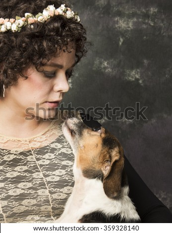 Pals/Pretty, stylish young woman looking down at small, mixed-breed dog as dog looks up at her against portrait background