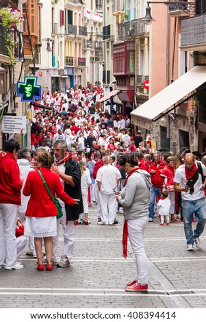 PAMPLONA, SPAIN - JULI, 09,2014: The people in festive clothes during San Fermin. Fiesta in Pamplona, which has been held annually for more than eight centuries and lasts one week â?? from 6 to 14 July. - stock photo