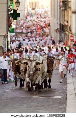 PAMPLONA, SPAIN-JULY 9: Bulls and men running in street during San Fermin festival in Pamplona, Spain on July 9, 2013. - stock photo