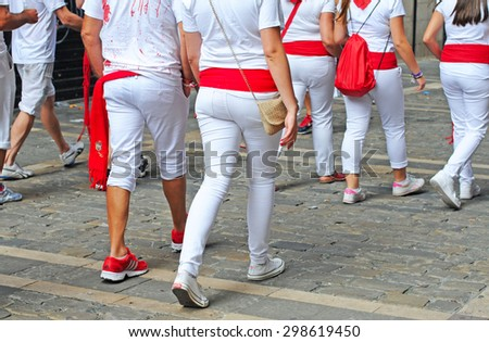 PAMPLONA, SPAIN - JULY 8, 2015: During the famous traditional annual feast of San Fermin, July 6 to 14, all inhabitants and most visitors are dressed in the city colours red and white - stock photo