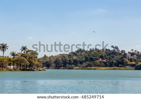 Pampulha lagoon with a airplane in the blue sky in a sun day.
