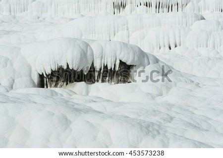Pamukkale (cotton castle) natural wonder is created by a layers of white travertine looking like cotton, Turkey. Natural pamukkale wall against a blue sky - stock photo