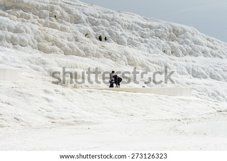 PAMUKKALE, TURKEY - APR 18, 2015: Unidentified tourists walk on the travertines of Pamukkale, Turkey. It's a UNESCO World Heritage site